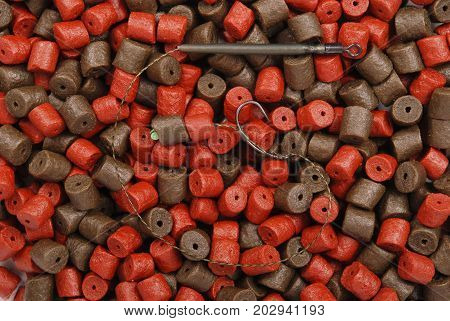 Fishing bait with hook and brown with red pre-drilled halibut pellets for carp fishing background