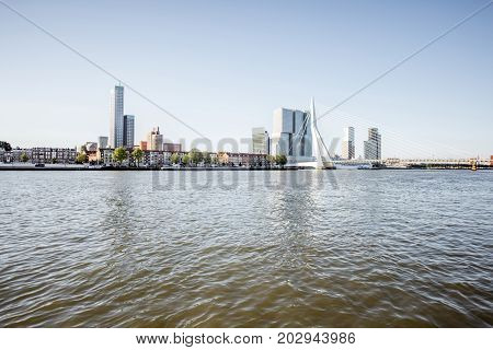 Landscape view on the beautiful riverside with skyscrapers and bridge during the morning in Rotterdam city