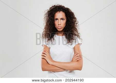 Offended curly woman looking at the camera with crossed arms over gray background