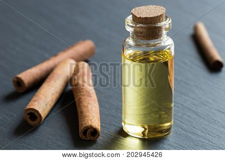 A Bottle Of Cinnamon Essential Oil With Cinnamon Sticks In The Background