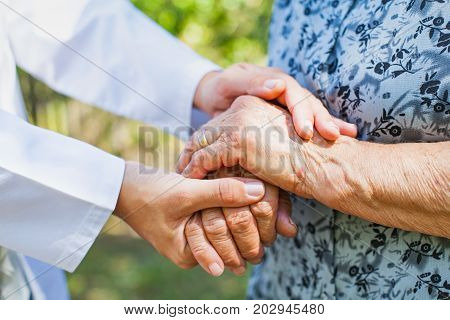 Close up medical doctor holding senior woman's shaking hands Parkinson disease