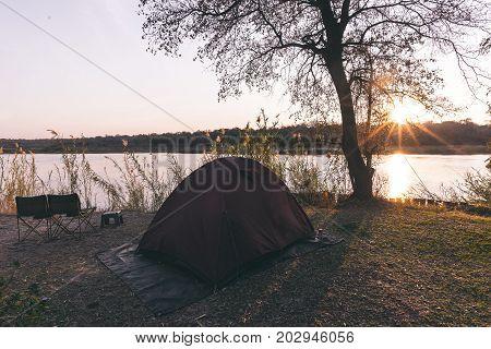 Camping Tent, Chairs And Camping Gear. Sunrise Over Okavango River, Namibia Botswana Border. Adventu