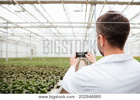 Back view of man gardener making photo of greenery on smartphone