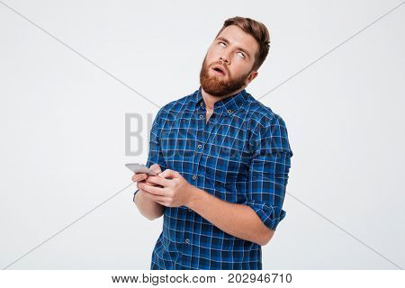 Dissatisfied bearded man in checkered shirt using smartphone ovver gray background