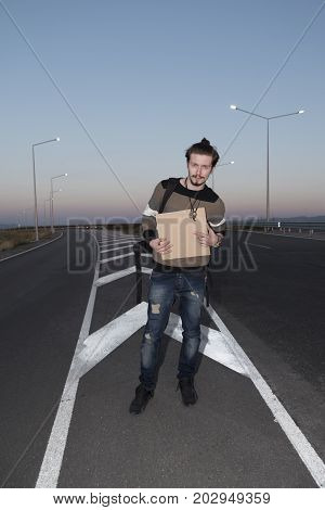 Young 21 years old man hitchhiking. Sunset