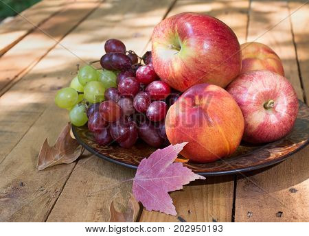 Plate of apples peaches and grapes on a wooden surface