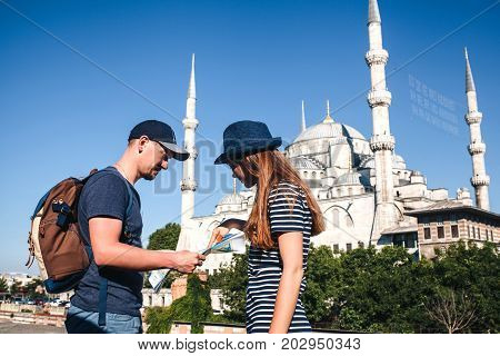 A couple of tourists a young man and a pretty woman look at the map next to the world-famous Blue Mosque also called Sultanahmet in Istanbul, Turkey.