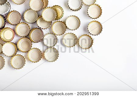 many upturned lids from beer scattered on a white background space for text