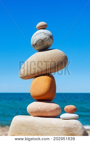 Rock zen pyramid made of colored stones on a background of blue sky and sea. Concept of balance harmony and meditation