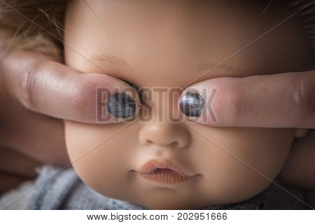 Fingers covering eyes of a doll, concept