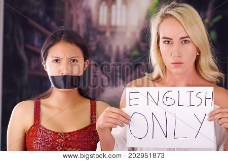 Young mad american blonde woman holding a piece of paper with a description of make america great again, while latin is with a black tape in her mouth, racism, violence or discrimination concept.
