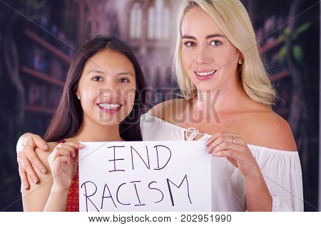 Two young women blonde and latin girl smiling and breaking racism idiosyncrasy from a american person and foreign people, holding a piece of paper that is written end racism. Racism, violence or discrimination concept.