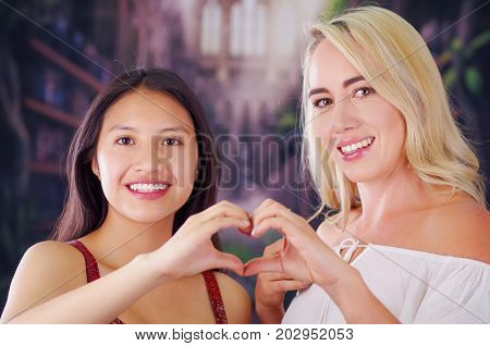 Two young women blonde and latin girl smiling and breaking racism idiosyncrasy from a american person and foreign people, both doing a heart sign with teir hands, racism, violence or discrimination concept.