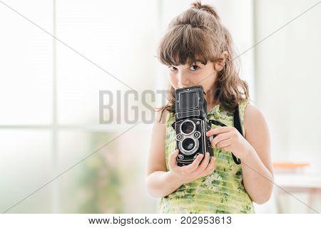 Cute photographer girl holding a vintage twin-lens reflex camera