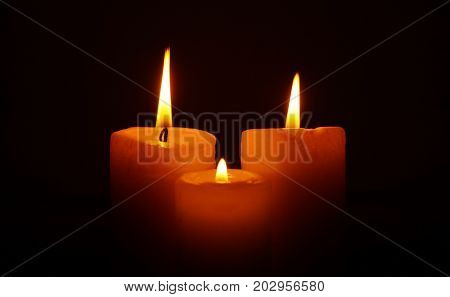 Three burning candles in the darkness. Mournful fire of candles. Fire of sorrow. Tragic state.