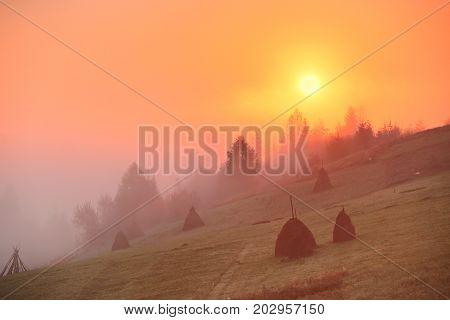 Sunrise Over Mountain Field. Haystacks In Misty Autumn Morning Hills.