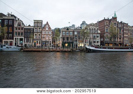 View Of Typical Amsterdam Houses Along Canal On Cloudy Sky.