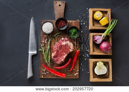Raw rib eye steak with herbs. Fresh meat with chilli on wooden desk. Cooking ingredients for restaurant dish in wooden boxes with onions and corn, top view.