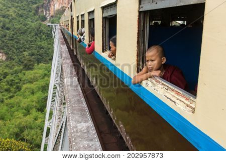 Hsipaw, Myanmar - October 4, 2016: Buddhist novice monk looking out of train that passing the famous viaduct Goteik between Pyin Oo Lwin and Hsipaw in Myanmar