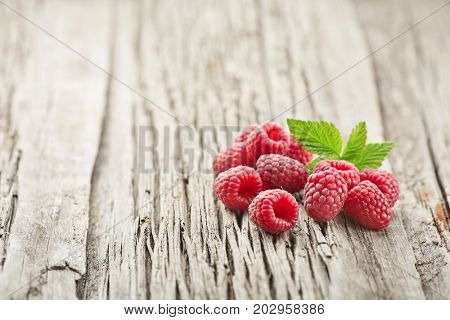 Fresh raspberry with leaves on a wooden board