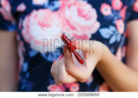 A girl is holding a popular toy fidget spinner in her hands. Stress relief. Anti stress and relaxation fidgets, spinner for tired people. Girl playing with a red fidget spinner.