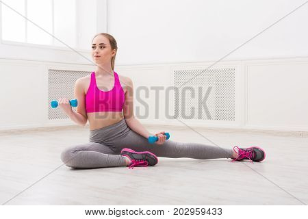Fitness woman workout training with dumbbells. Young girl in fitwear at white background