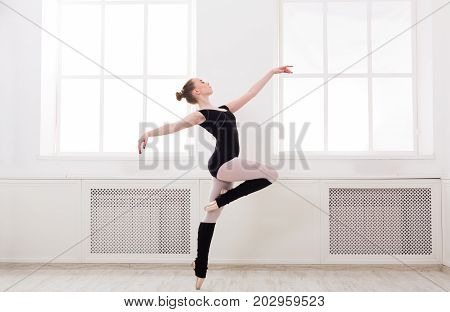 Young graceful ballerina in black at ballet class making pirouette. Classical dancer in white hall practicing positions near large window, copy space