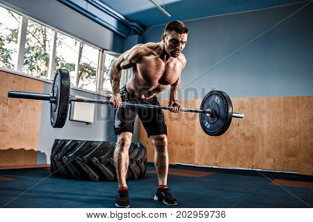 Strong bearded tattooed man at a crossfit gym lifting a barbell.