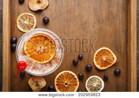 Dry orange, lemon, apple sliceces, chocolate sweets and coffee punch on wooden board. Candied citrus citrons top view with copy space. Confectionery, bar or christmas background concept