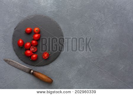 Cut tomatoes on rustic slate stone plate. Cooking healthy food on gray background, copy space, top view.