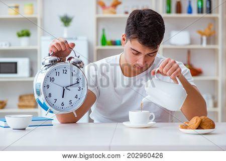 Man with alarm clock falling asleep at breakfast
