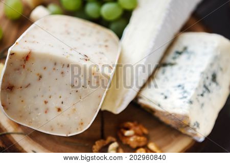 Different sorts of cheese bsckground. Hard cheese with herbs, brie and blue cheese as pieces with grapes and nuts. Still life, selective focus