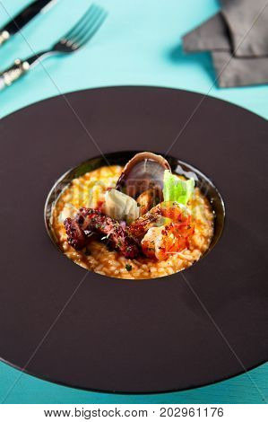 Risotto Tom Yam with octopus, shrimps and salmon with seasonings and fresh herbs. Served dish with cutlery on a blue wooden table. Gastronomic restaurant menu