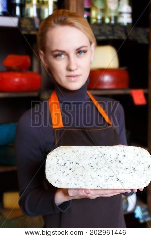 Gouda pesto cheese. Female shop assistant suggesting cheese with herbs, grocery shop background