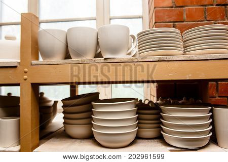 A Pottery. White Bowls And Plates Are On Shelves Of The Cupboard