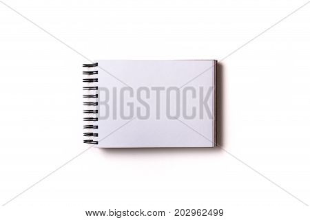 Horizontal aligned isolated sketchbook mock up with blank white sheets on white background. Top view flat lay.