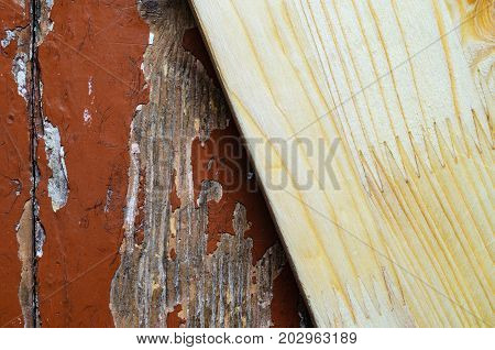 Glued board on old dilapidated wooden floor with brown peeling paint.