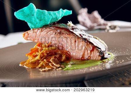 Salmon sous vide with julienne of stewed vegetables and fresh herbs on decorated ceramic dish. Gastronomic restaurant menu