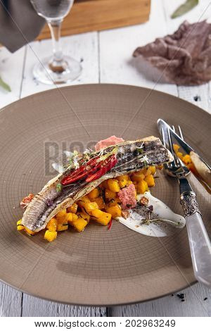 Fish-hare with spicy pineapples and coconut milk with sauce and fresh herbs on ceramic plate on the background of blurry wine glass with drink. Gastronomic restaurant menu