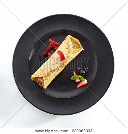Dessert in restaurant. Fried pancake with ice-cream and fresh berries, sprinkled with syrup and with mint leaves in black plate. Top View