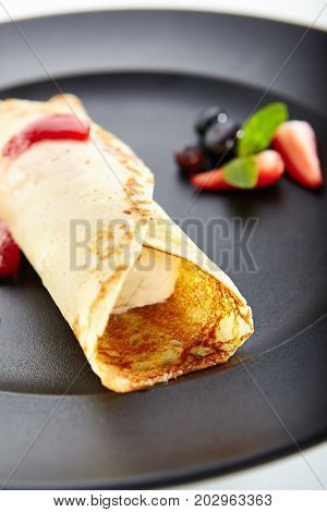 Dessert in restaurant. Fried pancake with ice-cream and fresh berries, sprinkled with syrup and with mint leaves in black plate