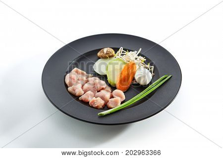 Teppanyaki Japanese and Korean Grill Food - Chicken with vegetables with fresh herbs and mushrooms on black plate on white isolated background. Preparation of raw food for frying on teppan