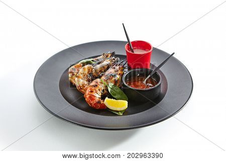 Teppanyaki Japanese and Korean Grill Food - 6/8 Shrimp Grill with fresh herbs and sauces on black plate
