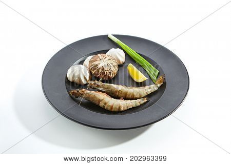 Teppanyaki Japanese and Korean Grill Food - 16/20 Shrimp with mushrooms with an lemon slice and fresh herbs on black plate on white isolated background. Preparation of raw food for frying on teppan