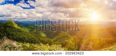 Carpathian mountains summer landscape with dramatic clouds and mossy stones. Panoramic view with sun shining