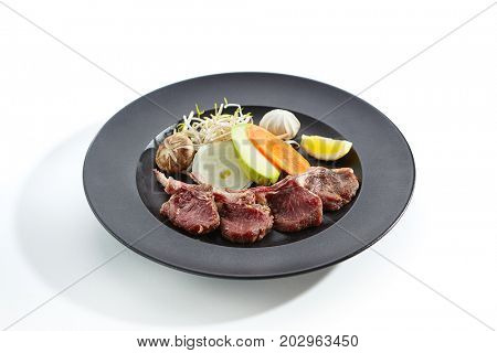 Teppanyaki Japanese and Korean Grill Food - Rack of lamb with vegetables and mushrooms with sprouts and lemon slice on plate on white  background. Preparation of raw products for frying on teppan