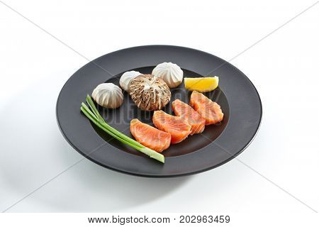 Teppanyaki Japanese and Korean Grill Food - Salmon with mushrooms with slice of lemon and fresh herbs on black plate on white isolated background. Raw product for frying on teppan