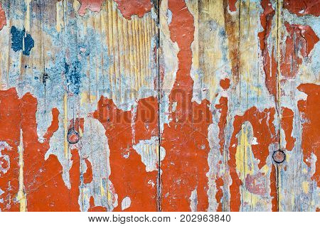 Texture of old dilapidated wooden floor with red peeling paint. Exfoliated Paint on an Old Wooden Floor