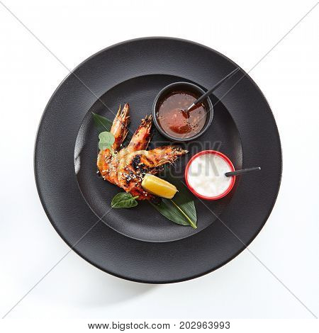 Teppanyaki Japanese and Korean Grill Food - 16/20 Shrimp Grill with lemon slice, fresh herbs and sesame and sauces served in black plate