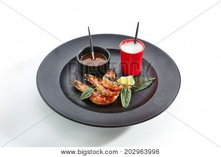 Teppanyaki Japanese and Korean Grill Food - 16/20 Shrimp Grill with lemon slice, fresh herbs and sesame and sauces served in black plate. Top View